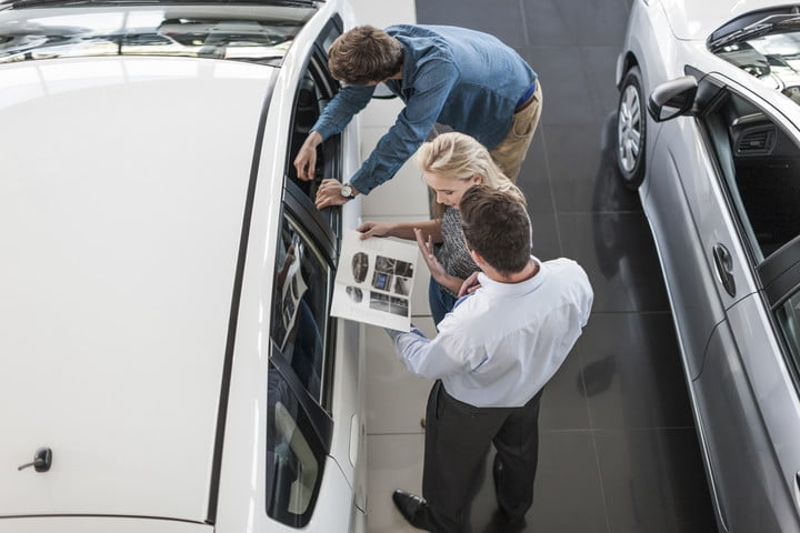 road rave subscription direct sales threaten traditional car dealers dealer showing brochure to young couple in showroom
