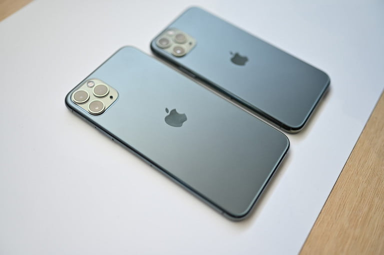 The backside of an iPhone 11 Pro Max and Pro, set on a table.