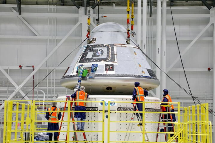 Technicians observe Boeing's Starliner crew module being placed on top of the service module in the Commercial Crew and Cargo Processing Facility at NASA's Kennedy Space Center in Florida on Jan. 14, 2021. The Starliner spacecraft is being prepared for Boeing's second Orbital Flight Test (OFT-2). As part of the agency's Commercial Crew Program, OFT-2 is a critical developmental milestone on the company's path to fly crew missions for NASA.