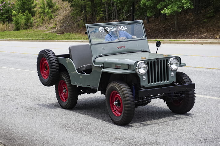 Side shot of teal classic jeep with spare tire on the back