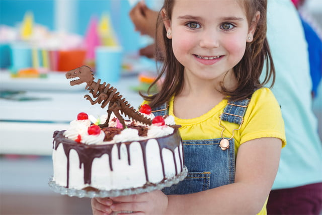chocolate construction t rex smiling girl holding birthday cake at the party