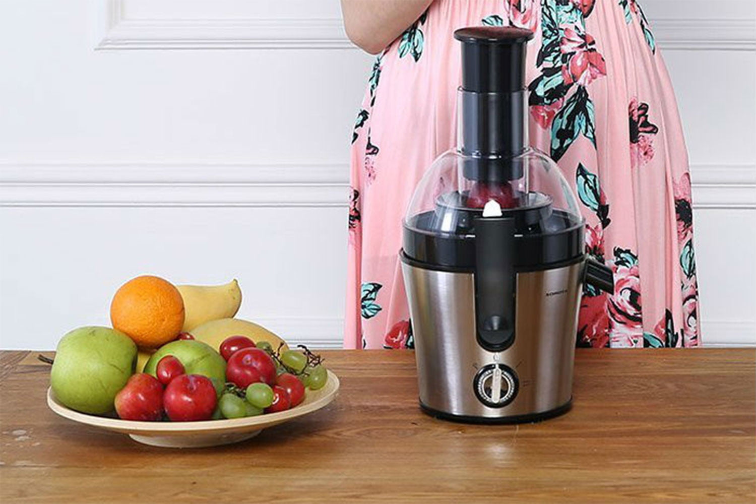 the girl is standing next to the juicer