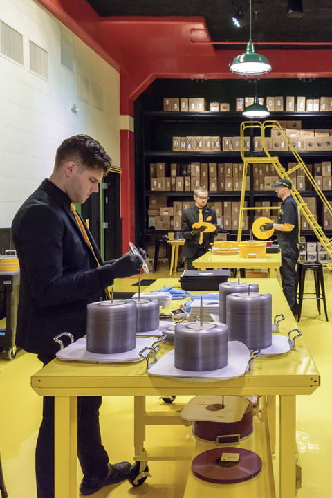 man-placing-records-into-covers-with-stacks-of-vinyl-around-vertical